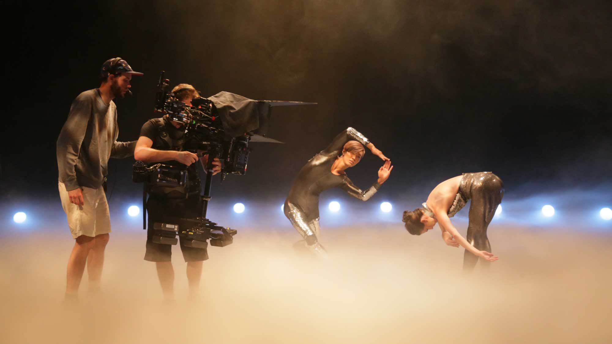 two camera operators shooting two dancers standing in fog