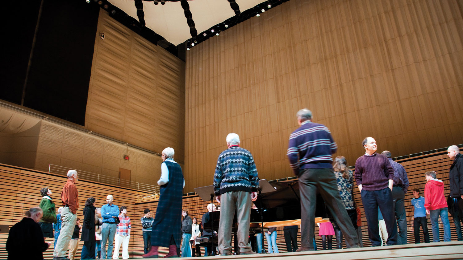 listeners circumnavigate a piano on stage in the concert hall