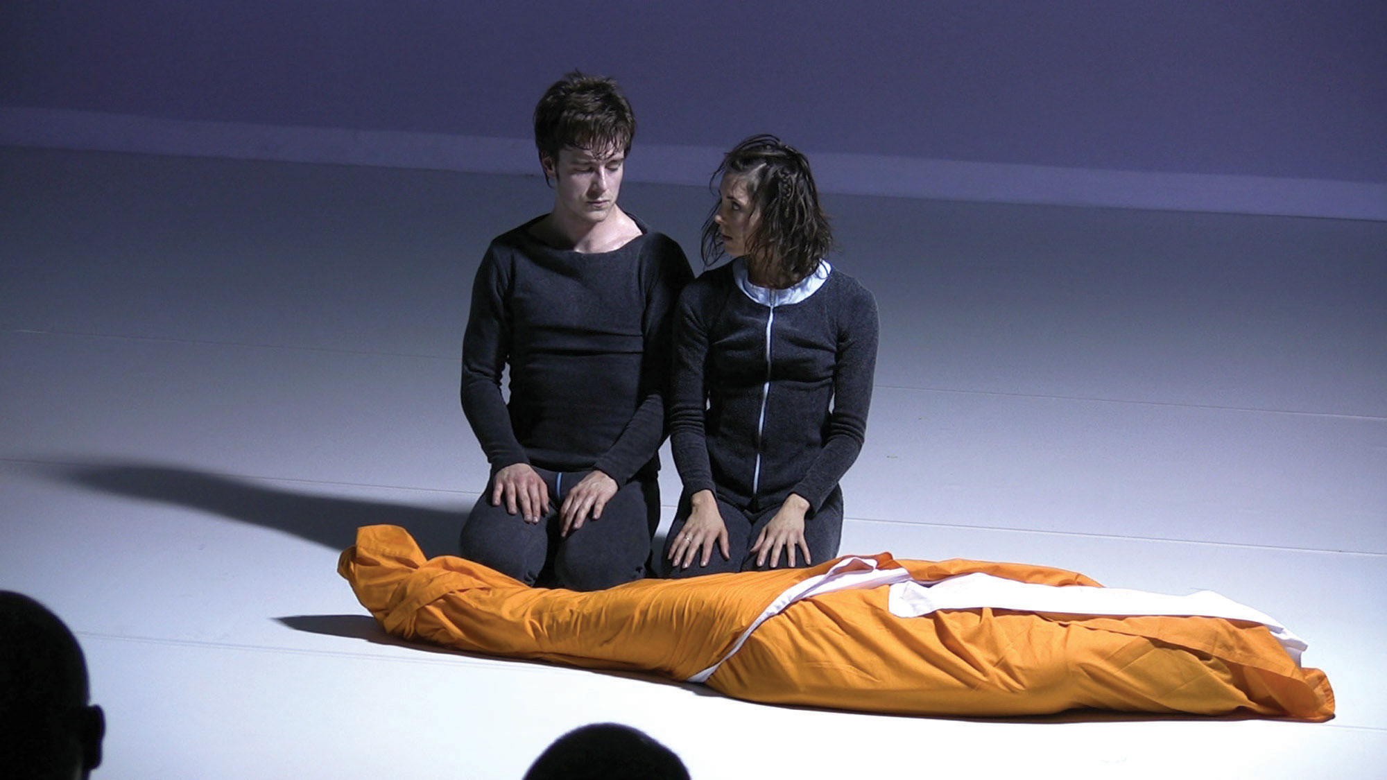 two people kneeling in front of a body wrapped in orange cloth