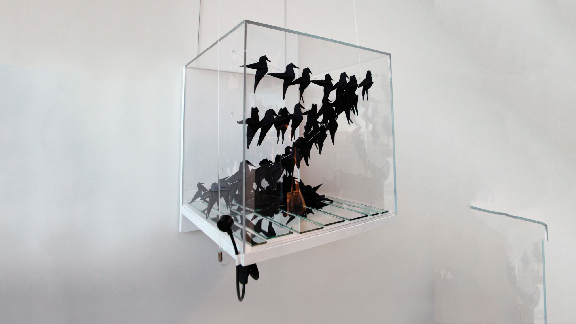a plexiglass box with paper birds