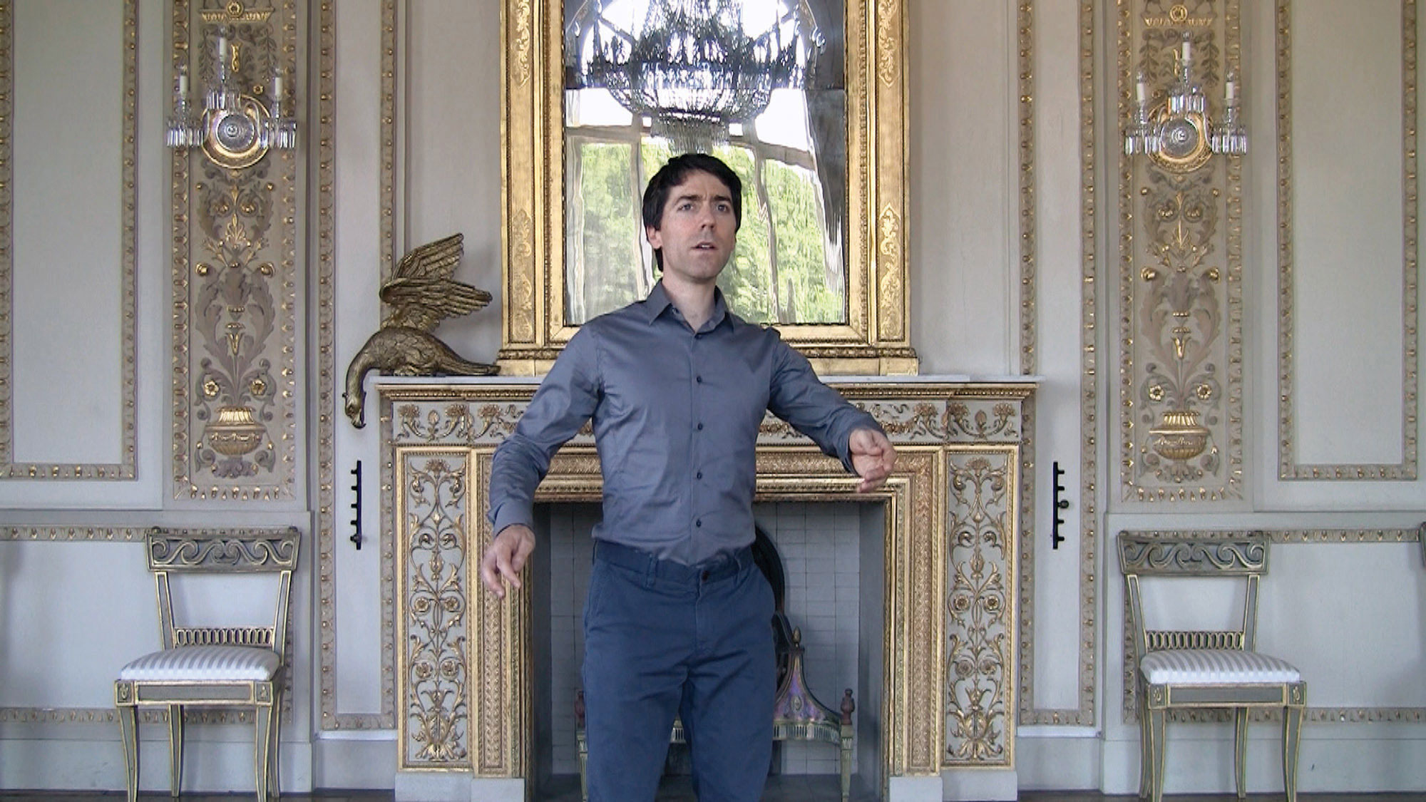 a man in blue standing in a baroque room.