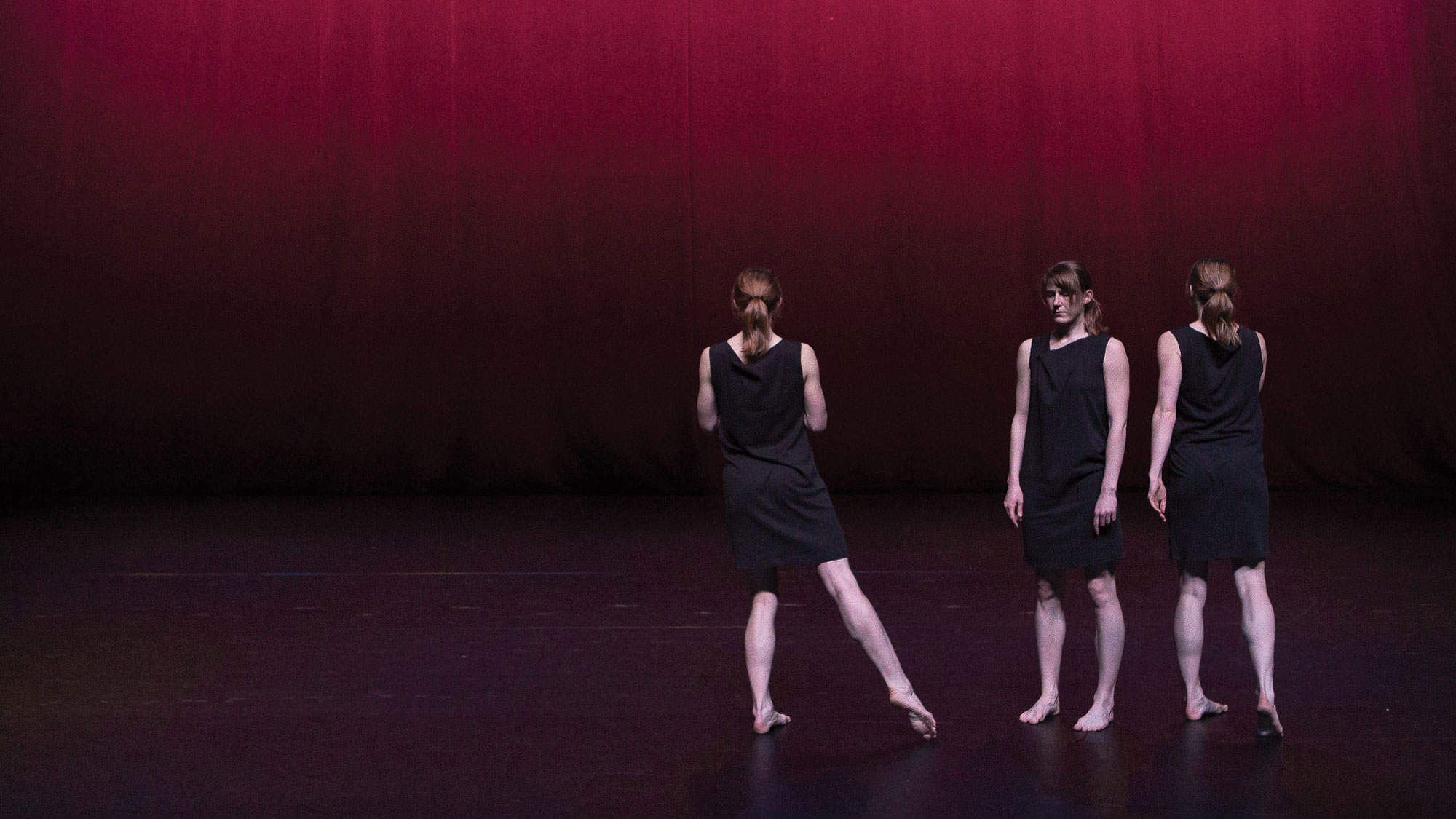 three dancers in black on stage