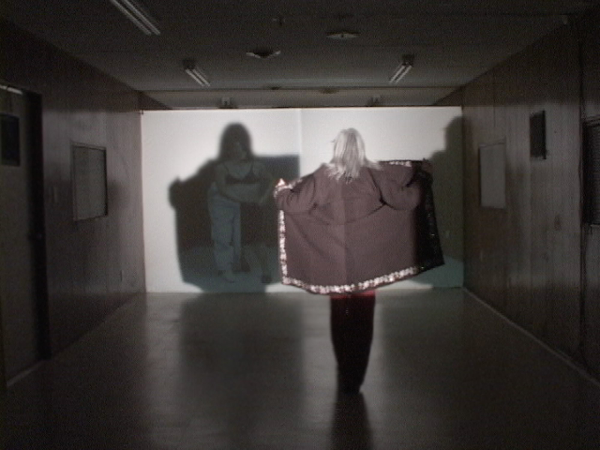 a woman creates a shadow with her jacket against a screen.