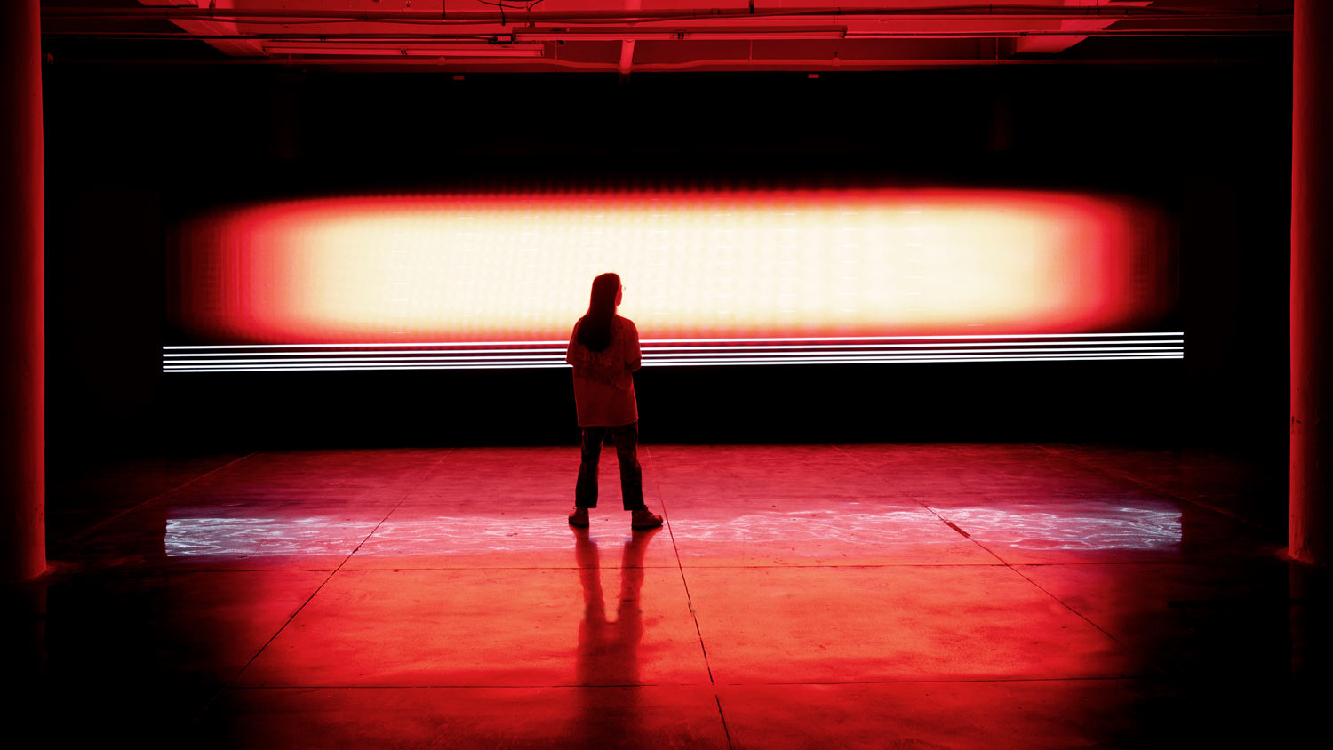 a strip of red light in a completely dar space, shadows of people in the foreground.