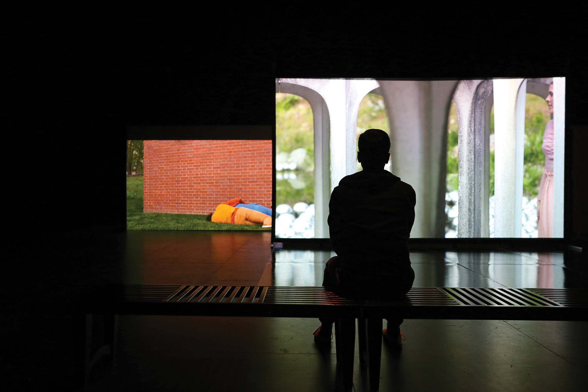 a man in the forground viewing a large video screen.