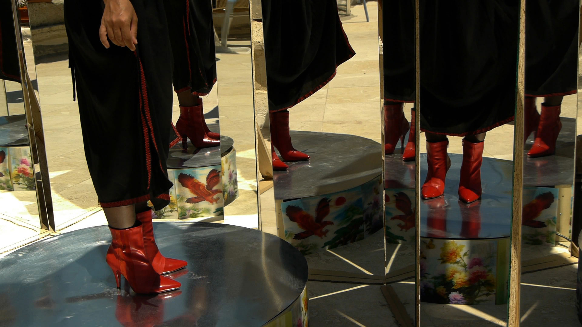 a person from the waist down standing with red stiletto ankle boots looking in a mirror