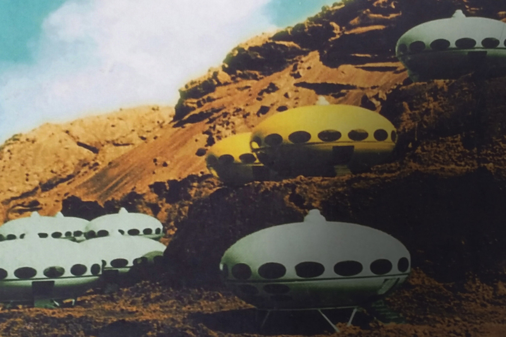a still from futuro, spaceship oval residencies set against an arid landscape