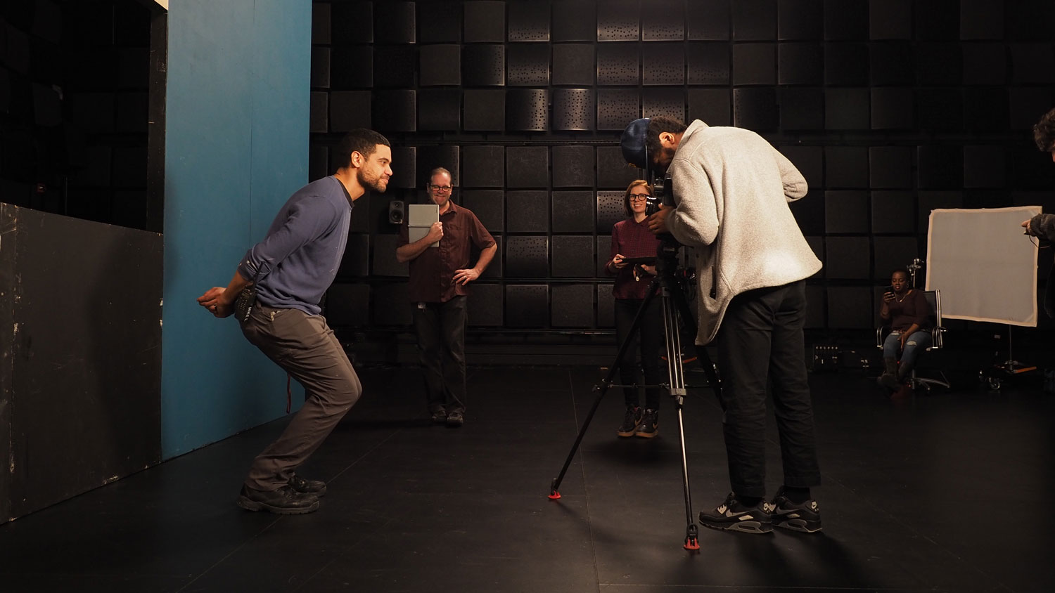 a man behind a camera filming a man against a blue backdrop, with staff in the background