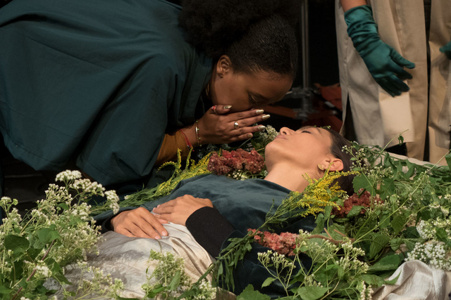a woman laying in a coffin covered in flowers while a dark-skinned woman whispers to her
