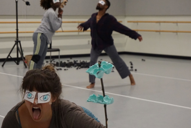 a woman with paper eyes stick her tounge out with dancers in the background