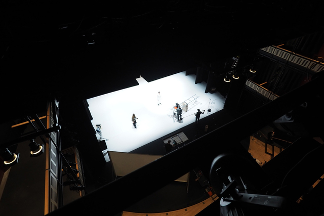 looking down on a white stage from the theater grid