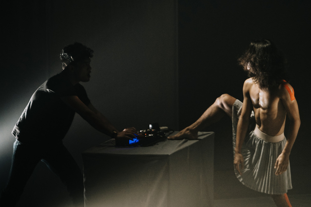 a man on stage at a keyboard with a trans dancer with his leg on the table