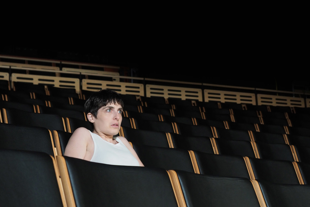 a woman in a white tanktop sitting in a theater alone, staring at the stage with wide eyes