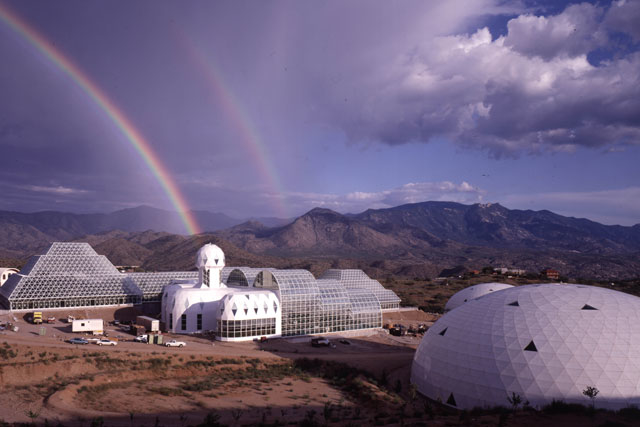 a bucky dome in the foreground, biosphere 2 in the background on a desert plain with a double rainbow in the sky