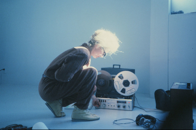 Maryanne Amacher kneeling in front of a film projector c 1970