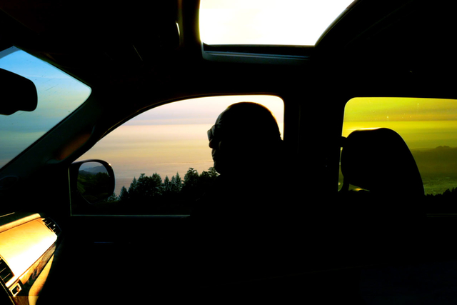 a silouette of a man in the passenger side of a car with the window and sunroof open