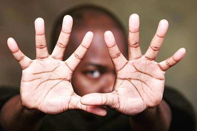 a bald black man with his hands extended in front of his face