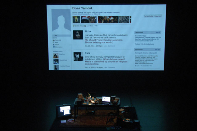 a woman in the theater in front of a projection of a facebook profile