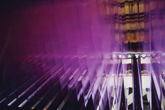 an video still of purple-cast water projected on geometric surfaces