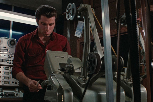 john travolta standing behind a projector in a projection booth.