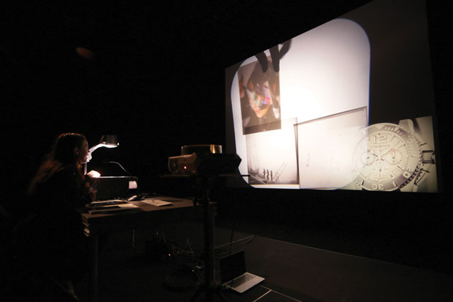 a woman in a theater controlling a projection