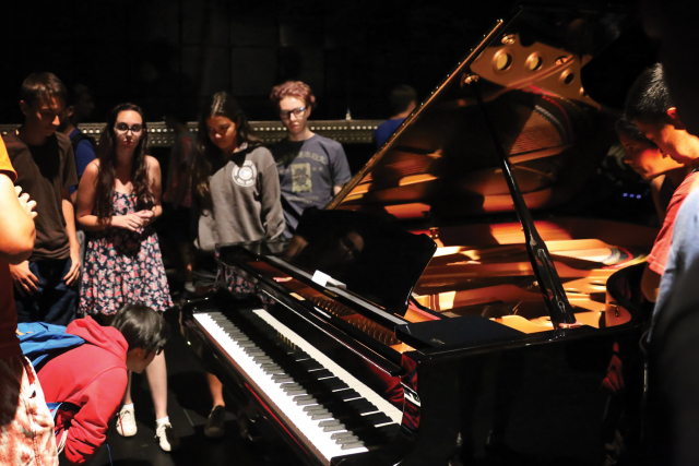 students standing around a piano in studio 1