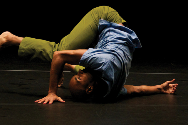 a black man on the stage floor with his leg over his head