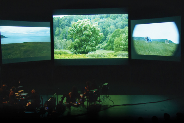 three screens in the theater with a band playing below.