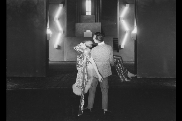 a man holding a woman in a dress in the 1920s in front of a art deco set.