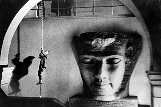 a man on a rope decends next to a massive granite carving of a head in the film still of blackmail