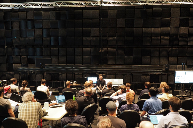 A woman and a man sitting at a table with computers in EMPACs Studio 1 during the 2017 Spatial Audio Workshop.
