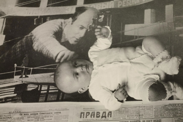 a black and white russian poster wiht a man reaching out towards a baby.