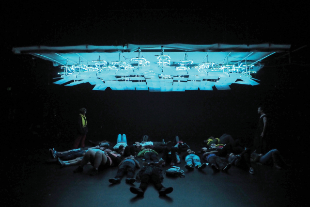 a group laying under a grid of lighted squares on the theatre stage