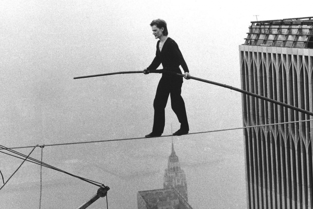 a man walking across the world trade center on a wire in NYC