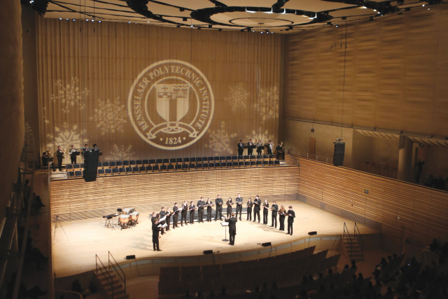 a group of student musicians on the concert hall stage.
