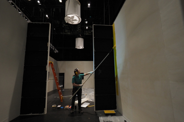 a woman painting a set in studio 1