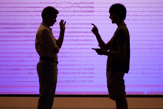 Two men standing in front of a projection of sound waveforms.