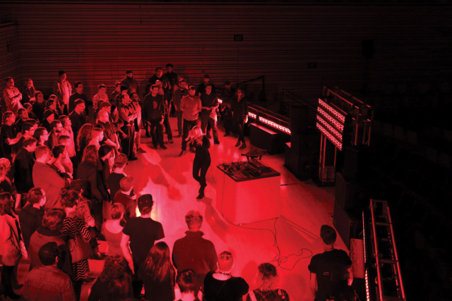 Pharmakon performing on the concert hall stage at EMPAC with an audience standing around her.